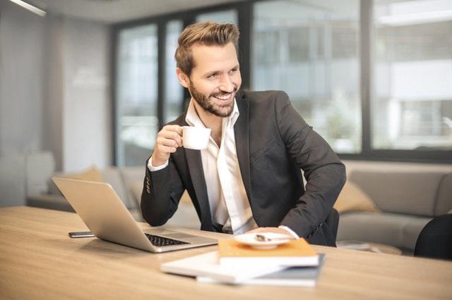 usměvavý muž v košili a saku pije z hrníčku, sedí za stolem a má před sebou notebook