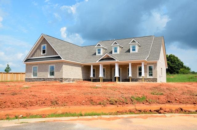 dům již skoro postavený světlé barvy s šedou střechou, před ním neupravený písčitý terén