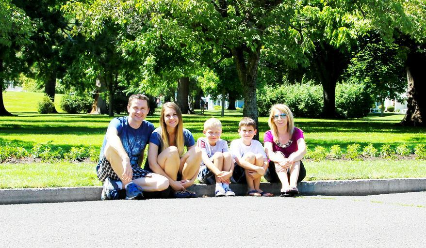 rodina sedící na kraji cesty u trávníku a parku